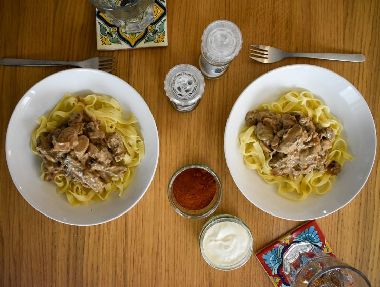top shot of two bowls of served beef stroganoff with pasta.