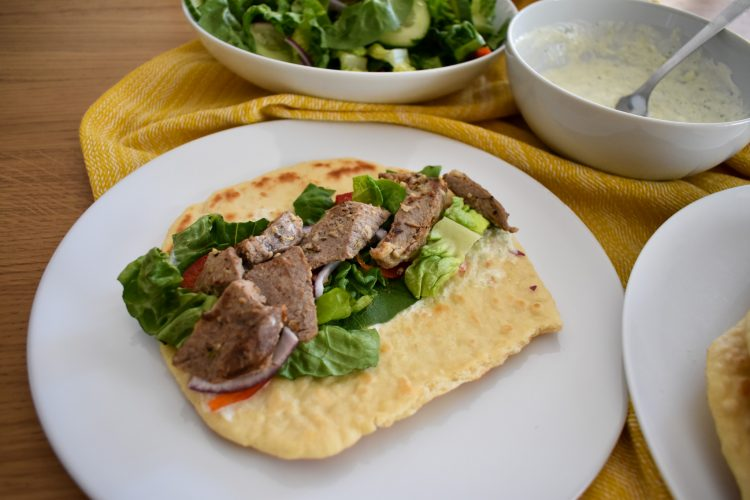 3/4 shot of unrolled leftover roast lamb greek wrap with salad. Bowl of tzatziki and salad in the background