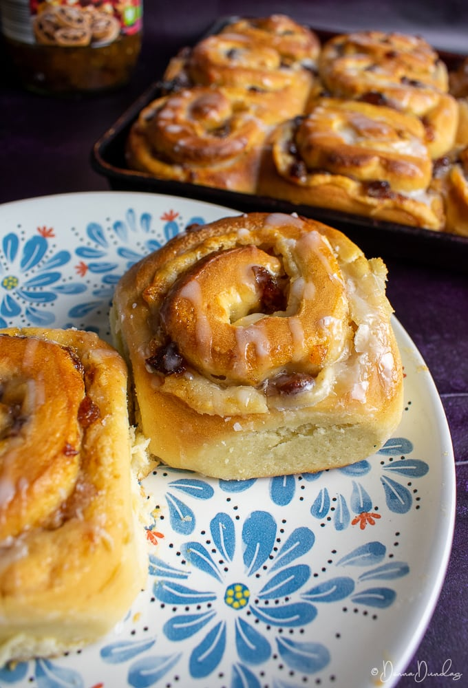 Mincemeat Chelsea bun on a patterned plate, other buns in background